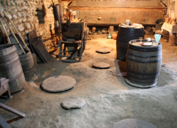 ashusPhotography- The wine cellar with empty barrels, wine making tools, pots, and jars